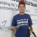 Rosenie Sarmiento, Jr. receives a set of tools and his certificate after completing a TESDA course on welding.